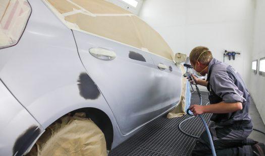 Un technicien repeint la carrosserie d'un véhicule