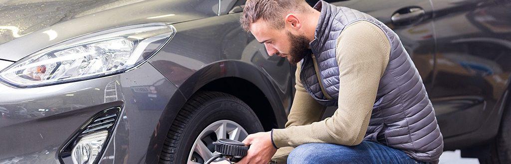 Un technicien réalise la pression des pneux après un changement de pneumatique